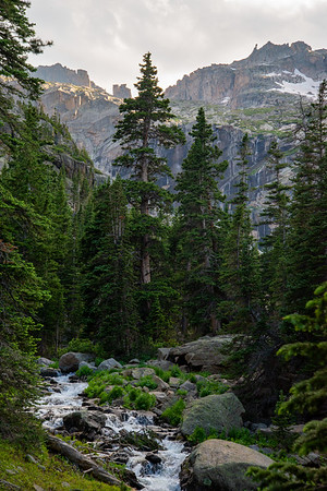 Waterfalls stream off of craggy peaks above dark forests deep in Rocky Mountain National Park in Colorado.