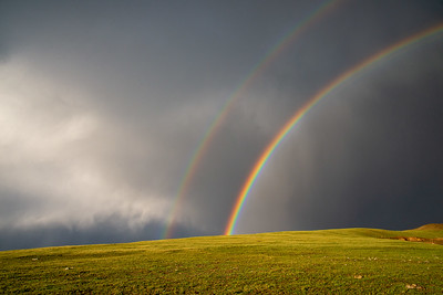 A double rainbow appears on the backside of a thunderstorm high on Trail Ridge in Rocky Mountain National Park in Colorado.