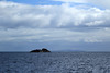 Fish Rock - Foveaux Strait - beyond to the Three Sisters, adjacent the southern headland peak into the New River Estuary, amongst the stratocumulus clouds above - Southland region.