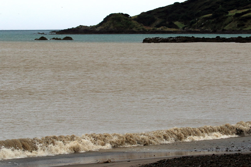 Wave breaking upon the shoreline along Whangaparaoa Bay - beyond the islets during mid-ebb tide, at the mouth of the Whangaparaoa River discharging its turbid water into the Southern Pacific - to Kopongatahi Point - the far northeasternmost area of the Bay of Plenty region.