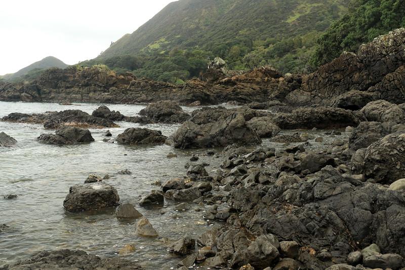 Volcanic basalt rock shoreline during late-ebb tide along the Mangaroa Range - beyond to the distal peak rising up to around 472 ft (144 m) above Lottin Point (Wakatiri), the northernmost point of the Raukumara Peninsula - Gisborne (East Cape) region.