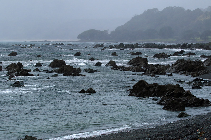 Waihua Bay - from the pebble/cobble shoreline, beyond the rock outcrops during mid-ebb tide, to Te Ahikehe Point - during a misty/rain mid-morning - the far northeastern area of the Bay of Plenty region.