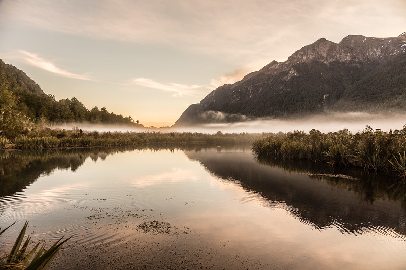 "The Mirror Lakes in New Zealand along the road from Te Anau to Milford Sound. Very easy to get to as its right by the road with a boardwalk along the shoreline. There is an upside down sign that reads ""Mirror Lakes"" which is right side up in the reflection - a nice touch! Only spent a few quick moments there was I was going back to town for the glowworm cave tour."