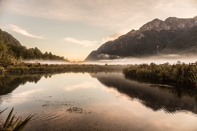 """The Mirror Lakes in New Zealand along the road from Te Anau to Milford Sound. Very easy to get to as its right by the road with a boardwalk along the shoreline. There is an upside down sign that reads """"Mirror Lakes"""" which is right side up in the reflection - a nice touch! Only spent a few quick moments there was I was going back to town for the glowworm cave tour."""