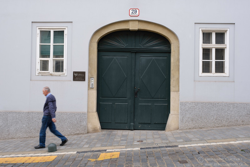 Man walking in front of a building in the historic Upper Town. Zagreb, Croatia