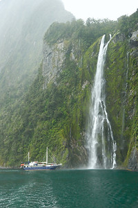 Misty Morning In Milford Sound © 2007 Colleen M. Griffith. All Rights Reserved.  This material may not be published, broadcast, modified, or redistributed in any way without written agreement with the creator.  This image is registered with the US Copyright Office. www.colleenmgriffith.com www.facebook.com/colleen.griffith  Milford Sound is one of the most famous destinations in all of New Zealand.  It's located in the Fiordland National Park on the South Island of New Zealand and was named a World Heritage Site because of it beauty.  Rudyard Kipling even named it the eighth wonder of the world.  It is actually a temperate rain forest - it is known as the wettest inhabited place in New Zealand and one of the wettest in the world.    Milford has hundreds of beautiful waterfalls year round.  This is the 155m (or 508 ft) tall Stirling Falls - you can see how stunning this waterfall is by comparing it to the triple-decker boat at the base (that boat has three levels and about 30 cabins for guests plus the crews quarters).  If you'd like to see the view of the waterfall from the boat, you can see it here: http://www.colleenmgriffith.com/Galleries/Travel-Destinations/New-Zealand/3907408_pWaRE#532245826_7qSEf  Other than a slight increase in contrast, this photo is straight out of the camera.