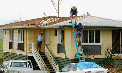 28 MAR 2006 INNISFAIL, QLD - The town of Innisfail is starting to return to normal a week after Larry's onslaught.  Contractors and volunteer tradesmen assist in the mammoth task of re-roofing Innisfail homes - PHOTO: CAMERON LAIRD (Ph: 0418238811)