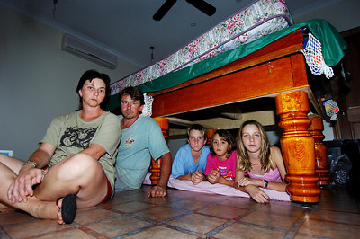 23 MAR 2006 INNISFAIL, QLD - Cyclone Larry damage in North Qld.  Kim and Wally Glatthor with children (from left) Zak, 12, Teshia, 8, and Hanna, 11 lay under the pool table where they spent hours huddled during Larry's onslaught - PHOTO: CAMERON LAIRD (Ph: 0418238811)
