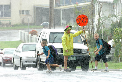 27 MAR 2006 INNISFAIL, QLD - Re-opening of Innisfail State School.  Crossing supervisor Shirlene Forsyth watches students make their way to Innisfail State School as it re-opens after being closed for a week following Cyclone Larry - PHOTO: CAMERON LAIRD (Ph: 0418238811)