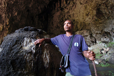 "04 MAY 2005 RAMPAPASA VILLAGE, FLORES, INDONESIA - Guide Agustinos Mangga in the cave near Rampapasa where ""The Hobbit"", a skeleton of a tiny woman who lived there 18,000 years ago was found.  Agustinos, who is half blind,  holds the keys to this archaeological site and has been making a living taking media, researchers and tourists to the now-famous cave - PHOTO: CAMERON LAIRD"