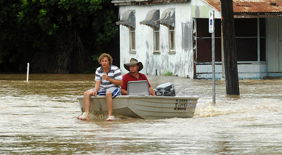 03 FEB 2007 Townsville, QLD - Flooding in the north Queensland sugar town of Giru.  Andrew Blacklock and son Andrew drive their tinnie down the main street of Giru - PHOTO: CAMERON LAIRD (Ph: 0418238811)