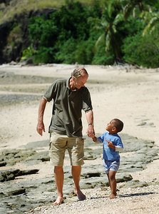 15 APR 2006 VOROVORO ISLAND, FIJI - Daily Mail writer Richard Shears walks along Vorovoro beach with one of the four island inhabitants, 4yr old Osea Rasavu Vuiravua - PHOTO: CAMERON LAIRD (Ph: +61 418238811)