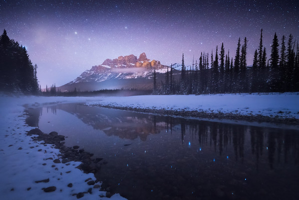 A cold winter night along The Bow River beneath Castle Mountain, Banff National Park, Alberta, Canada