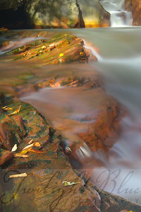"""Amber Rocks""  The amber rocks in the river below Douglas Falls, Douglas, West Virginia are unique to the region. Their color is a result of the acid deposits from the Acid Mines. To capture this image I perched myself on one of the rocks approximately 30 feet below the sides of the riverbank, placing my feet and tripod in the rushing water. The close-up angle shows the definition of hard lines of the rock contrasting with the flowing water with the 35 foot cascade in the background."