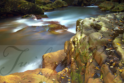 """Blackwater River""  Being a part of nature gives me a thrill. Sitting in a river trying to capture its fury gives me an even bigger thrill. This image taken in Blackwater River at the base of Douglas Falls, West Virginia on a cool autumn day epitomizes the strength of the river by the rocks it has molded.  The multiple exposure, High Dynamic Range (HDR) shot minimizes the harsh mid-day light shining on the slippery stone on what otherwise would have been considered a bad day to shoot waterfalls."