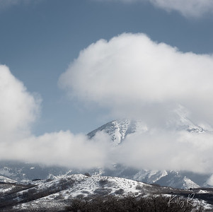 Peaking through the clouds. Box Elder Peak among the Wasatch Mountains.