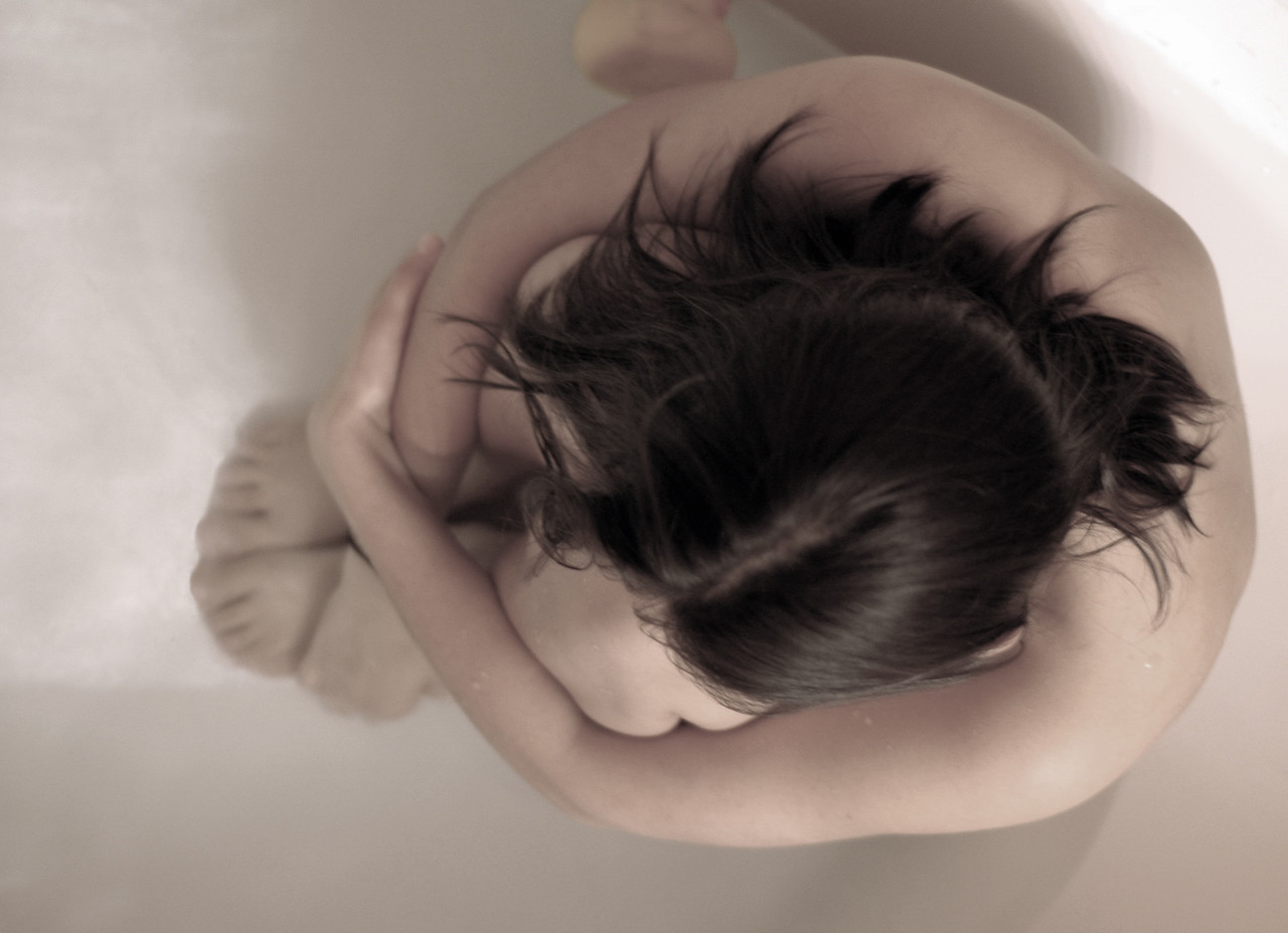 Young woman sitting in the bath, soft blur image