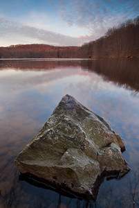 A large boulder dominates the sunset at Cross River Reservoir, Cross River, New York