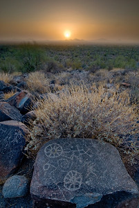 Sunset through a dust storm by the petroglyphs at Signal Hill, Saguaro National Monument, Arizona