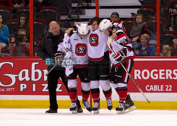 Adrian Sloboda being helped off the ice.  He sustained a high-ankle sprain falling awkwardly after a hit from Brock McGinn.