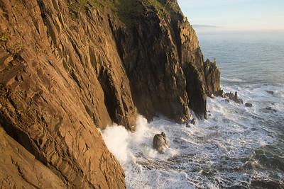 Waves crash into dramatic sea cliffs along the Oregon coast.