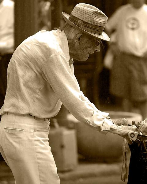 older gentleman pushing grocery cart in rain through downtown street in New Orleans