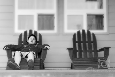 Soft diffused portrait of a boy sitting on one of the outdoor adirondack chairs shot in black and white.   © Copyright Hannah Pastrana Prieto