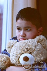 Soft diffused portrait of a boy holding a teddy bear looking outside the window on a rainy day.  © Copyright Hannah Pastrana Prieto