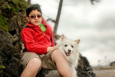 A boy with his American Eskimo dog sitting at the rocks of the beach  © Copyright Hannah Pastrana Prieto
