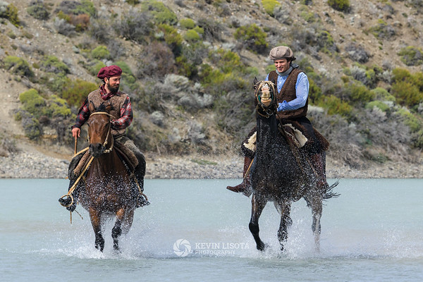 Gauchos on horseback in the La Leona River of Patagonia
