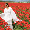 A woman in a white sari poses in the red tulips