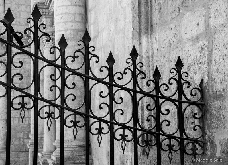 A black and white of the ornate iron gates at the side of the cathedral.