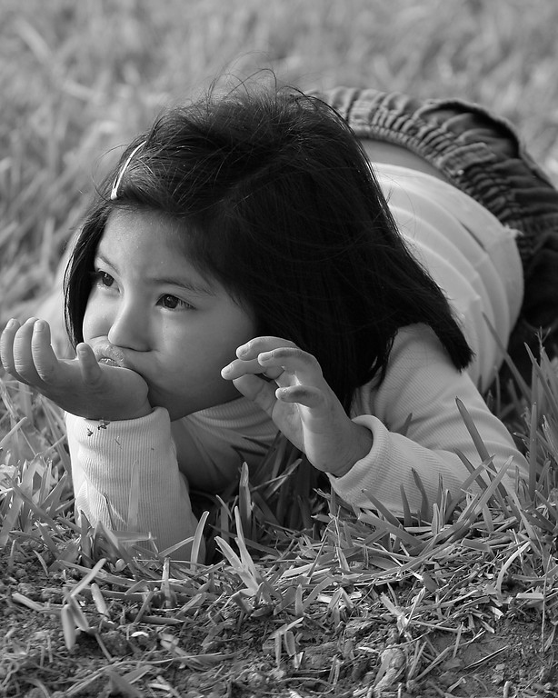 Pensive girl rests in grass Peru