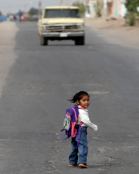 Sweet little girl on the way to school.  Obviously she was more interested in me than in the truck coming down the road in Bella Union, Peru
