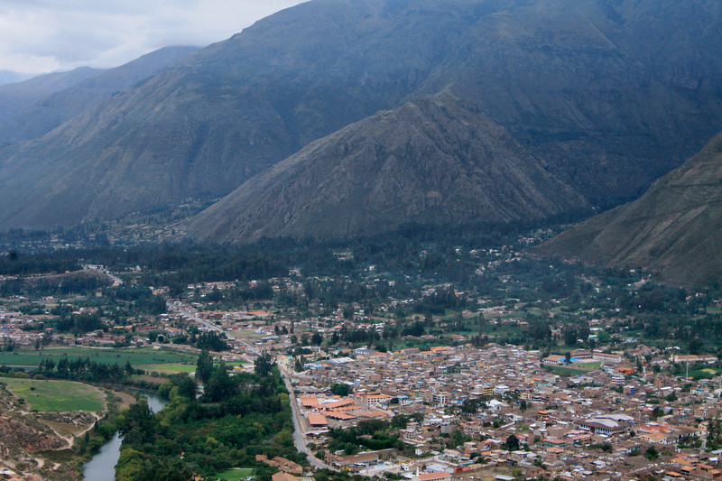 """Early morning down into the """"Sacred Valley of the Incas"""", also called the Urubamba Valley - with the Rio Vilcanota (also known as the Urubamba River) and the steep slopes of the southern end of the Urubamba Mountains along the Cordillera Oriental Andes - with the town of Urubamba thereamong - Cusco department."""