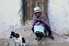 Elder Quechua women - wrapped in her colorful tied poncho blanket or shawl and wearing a fraying cloth hat - setting with her perro upon the stone steps, white-wash adobe wall, and wooden portal of her home - San Pedro de Casta.