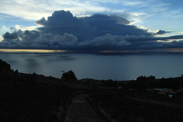 Eastward view from along the slope of Isla Amantani - to the storm cloud above Lake Titicaca, at sunrise.