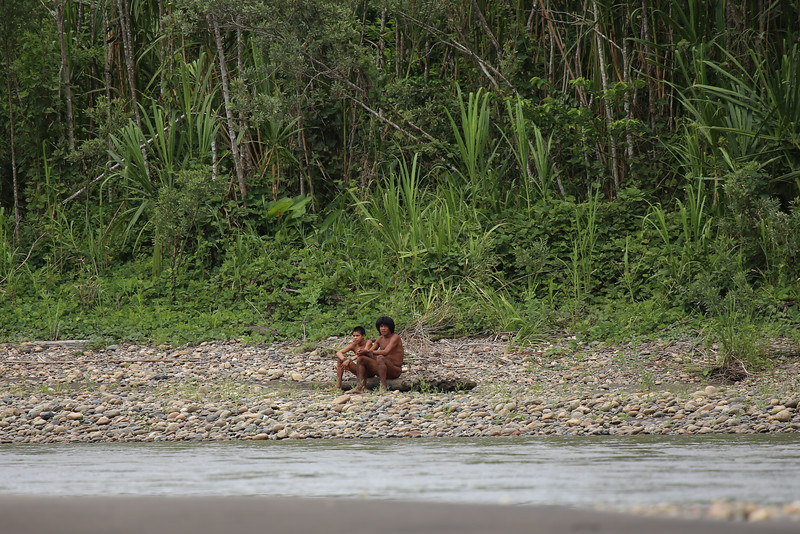 Young Mashco-Piro - setting upon a log along the rocky bank of the Mother of God River - in the Southwest Amazon Moist Forest ecoregion.