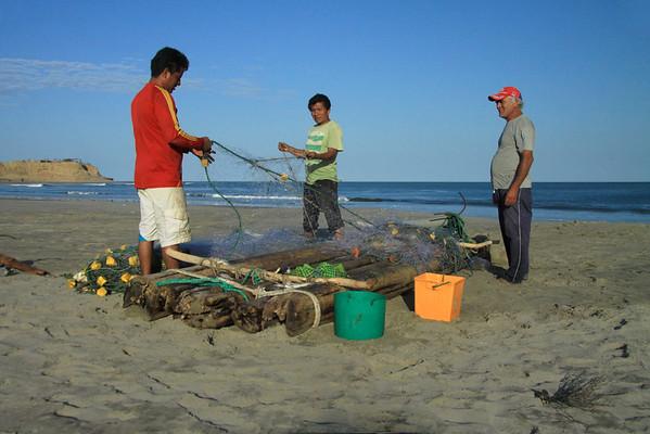 Pescadores tending to their fishing net adjacent their home-made raft - Organos village - Piura department.