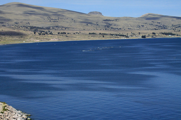 Commercial trout farming - upon Lake Titicaca - with the shoreline along the northern Chucuito province, and the peak of Cerro Pucara (c) - Puno department.