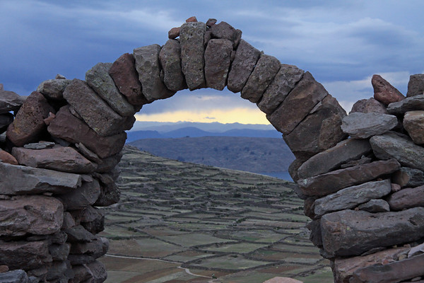 Thru the rock archway atop Isla Amantani, at Mount Llacastiti, upon Isla Amantani - viewing across the cultivated fields with rock wall fences - down to Lake Titicaca, and the Capachica Peninsula - with distal the Cordillera Occidental Andes (western) - and a storm developing about an hour before sunset - Puno department.