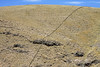 Hand-sacked rock forming a livestock fence across the steep rocky slope, scattered with tussock grass - Puno department.