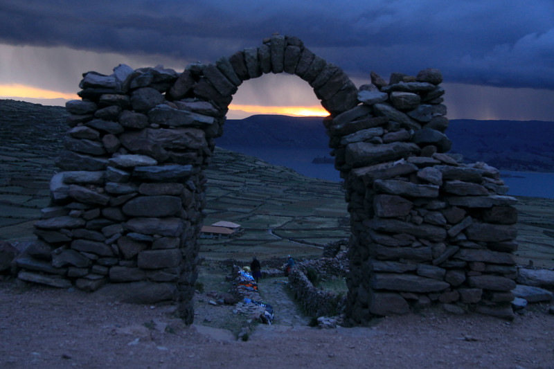 Sunset thru the stone archway atop Mount Llacastiti, adjacent th Pacha Tata ruins, upon Isla Amantani - with a storm cloud above Lago Titicaca and the Capachica Peninsula - Puno department.