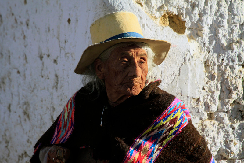 Ealry morning sunlight and shadows upon an elder Quechua woman - in the mountain village of San Pedro de Casta - Lima department.