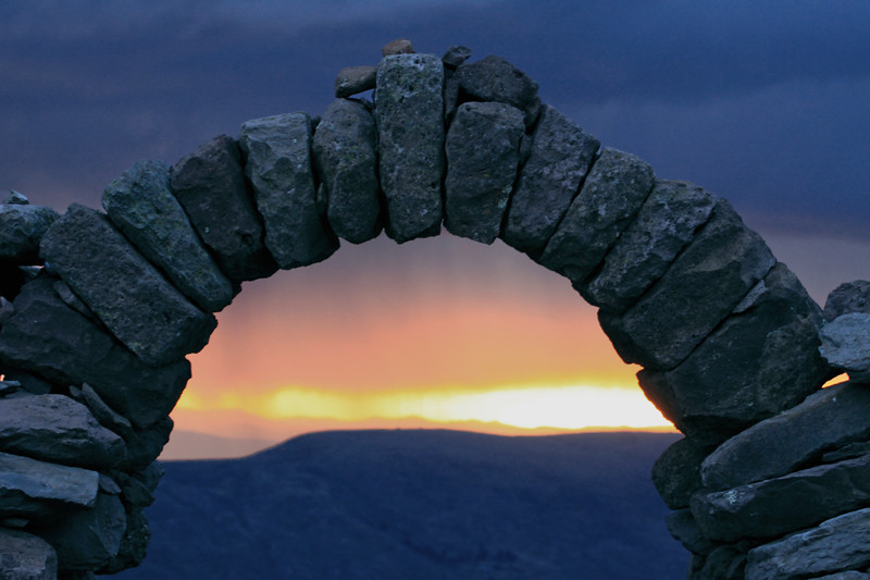 Thru the stone archway atop Isla Amantani (at the Pacha Tata ruins) - to the sunset beyond the ridge of the Capachica Peninsula and below a storm cloud - Lago Titicaca.