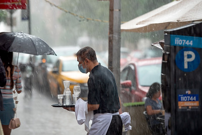 NEW YORK, NEW YORK - JULY 11: A waiter wearing a mask carries dirty dishes as it suddenly begins to rain as the city moves into Phase 3 of re-opening following restrictions imposed to curb the coronavirus pandemic on July 11, 2020 in New York City. Phase 3 permits the reopening of nail and tanning salons, tattoo parlors, spas and massages, dog runs and numerous other outdoor activities. Phase 3 is the third of four-phased stages designated by the state.