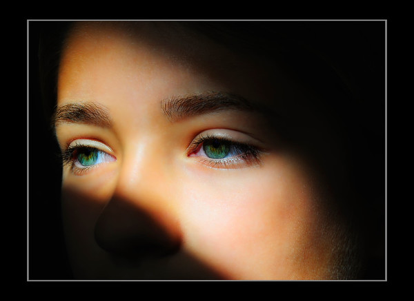 """<center><h2>""""Those Eyes""""</h2></center> <em><center>details best seen @ size X3</center></em> While walking through my kids TV room last night I noticed a great beam of natural sunlight coming through the front window as the sun was going down and then saw my daughter Alexa's eyes catching the light as well. So I made her get off the couch (I know I'm a terrible Dad LOL) and had her stare out of the window. I should have went to get my 50mm Nikkor or 90mm Tamron for this Portrait to get a sharper image but I was lazy and stuck with the 18-200 VR that was on the body but I think it did a fine job, impressed me really. When seen as large as possible you can see each individual eye lash reflected on her retina, pretty cool!  I then hit this with my normal Portraiture work flow & slight glamour treatment, removed a bunch of small hairs in between the nose, shaped her brows and did some very minor burning to bring out her cheek bone a little bit and that's it. The shadow is all natural just using proper exposure settings and shooting tight to prevent any of the background in the room from showing. Alexa's eyes are usually a nice blue but she was wearing a purple shirt which turns them a wild greenish aqua blue seen here. She's my favorite model and loves to have her photo taken so we both make out on the deal whenever I want to do a portrait to keep my skills sharp ;) I like this one so much I'll be ordering it in a large format lustre print or possibly a canvas to hang on my office wall! ~I just love my kids ~ Hope you all like it, Have a Great Day everyone !  <span style=""""color:red""""><em>PS: This image has been the #1 Rated photo on my site since it's post date. Please click on the 'Green Thumbs Up' sign over the image if you agree to keep it rated #1 </em></span>  ~Bill~"""