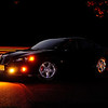 """<center><h2>""""My GXP At Sunset""""</h2></center> This is my 325hp 08' Pontiac Grand Prix GXP. I've been planning this shot out for a while now but had to wait for the right conditions which finally were available last night. It was a very technical shot and certain things had to come together in order for it to be successful including the orange sunset in the background, the moon in the front coming up early and then having a car drive behind me on the access road. The set was also a bit technical having to use several small LED flashlights to light the rims which were placed at 7 o'clock and 5 o'clock at different angels pointed upward from the ground to enhance depth and color of the rim reflection and a small street light above left for the hood. All of the colors you see here are NATURAL and have not been manipulated by photoshop what so ever. This image doesn't even have an adjustment layer on it, only a small amount of unsharp mask for the rims was used so I didn't disturbed the natural pattern of the long exposure of the fog/parking light rays or the tail lights going by giving the effect that my car had been moving from the rear (see tail lights how they match up with the car that went by). I actually took about 15 shots every time a car went by behind my car over the course of an hour (not very many cars travel this road) and I am located in a parking lot.  The exposure was 4 seconds at f/9 ISO 800 and a Custom dialed in Kelvin White Balance temp of 8680 to enhance the sunset and reflections, I also am using Center Weight metering to get my car in balance and not over exposed because I wanted it to look like a shadow & outline with the rims & hood lines being high lighted. The moon is directly behind me giving off the soft light on the side of the car & hood and the sun is setting behind my car which is obscured by the wood line and just peaks through the trees. Again this is almost as it was Straight out of the Camera besides a small amount of sharpening, it's"""