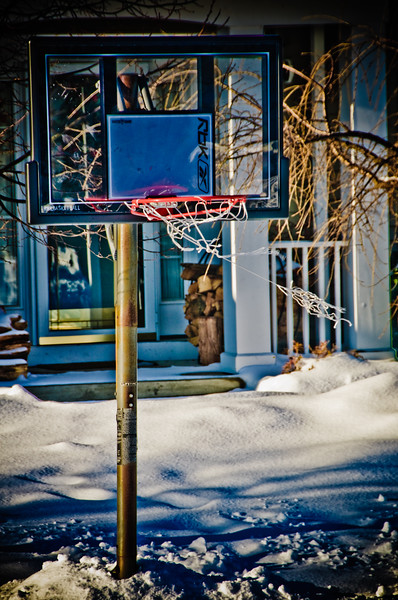 """Blowing in the Wind"" A shot of my neighbors basketball hoop that has taken some abuse during our many snow storms with the net showing wear & tears while it blows in the wind. This image has been post processed & tone mapped as a single frame HDR (*High Dynamic Ranging) photo to bring out the textures, colors, light & shadows."