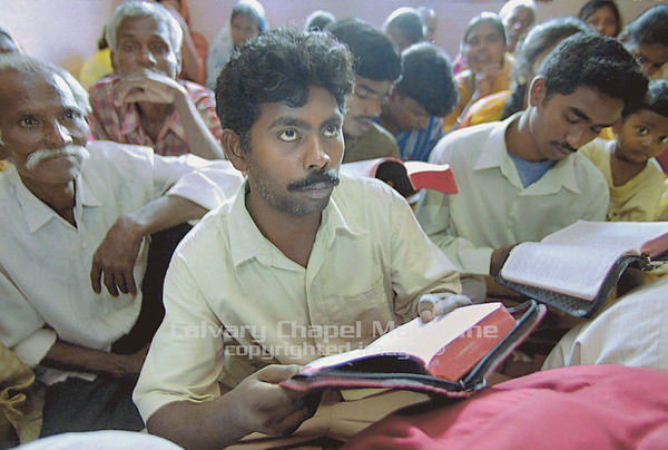 Men study the Bible in a crowded church in a Muslim area of Bangalore, India. Congregations are gender-segregated.